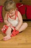 Il bambino sta mettendo sui pantaloni Fotografia Stock