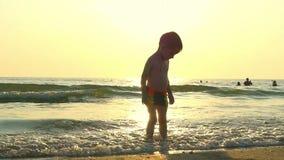 Il bambino sta nell'acqua sulla spiaggia del mare, nelle onde ricevute, contro lo sfondo di un declino all'rallentato archivi video