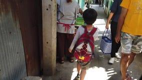 Il bambino sta passando una via locale di Bangkok archivi video
