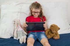 Il bambino sta riposando a casa Bambina 6, 7 anni che si siedono a letto con i giocattoli, esaminando la sua compressa, sorrident Immagini Stock