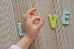 Il bambino sta scrivendo l'amore di parola da Toy Letters variopinto Fotografie Stock