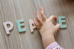 Il bambino sta scrivendo la pace di parola da Toy Letters Colourful Fotografia Stock Libera da Diritti