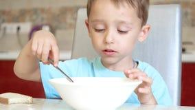 Il bambino sta sedendosi al tavolo da cucina, mangiante la minestra con un cucchiaio video d archivio