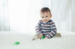 Il bambino sta sedendosi con le teste di legno a disposizione Immagine Stock