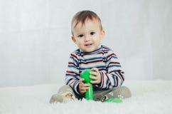 Il bambino sta sedendosi con le teste di legno a disposizione Immagini Stock Libere da Diritti