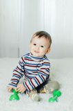 Il bambino sta sedendosi con le teste di legno a disposizione Fotografia Stock Libera da Diritti