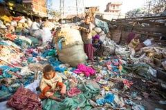 Il bambino sta sedendosi mentre i suoi genitori stanno lavorando allo scarico Immagine Stock Libera da Diritti