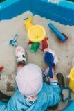 Il bambino sta sedendosi nella sabbiera Fotografie Stock
