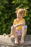 Il bambino sta sedendosi sul riposo del ceppo immagine stock libera da diritti