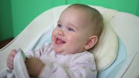 Il bambino sta sedendosi in una sedia del ` s del bambino e sta sorridendo, alto vicino archivi video