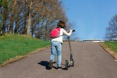 Il bambino sta spingendo il motorino sulla collina Immagini Stock