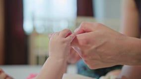Il bambino sta tenendo il dito del ` s della madre fotografia stock