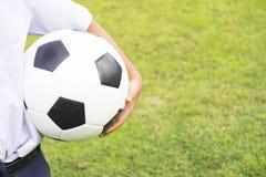 Il bambino sta tenendo il calcio su erba verde Fine in su fotografia stock