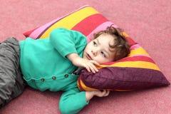 Il bambino sta trovandosi su tappeto Fotografia Stock