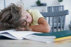 Il bambino stanco che dorme con la sua testa riposava su una tavola con un libro immagini stock libere da diritti