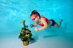 Il bambino subacqueo nello stagno decora l'albero di Natale con i giocattoli di Natale Ritratto Fucilazione sotto l'acqua Orienta immagine stock