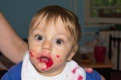 Il bambino sudicio e sporco sta mangiando lo spuntino Fotografia Stock