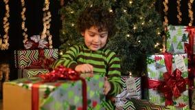 Il bambino sveglio apre il regalo di Natale stock footage