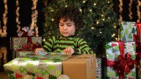 Il bambino sveglio apre il regalo di Natale video d archivio