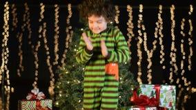 Il bambino sveglio balla emozionante davanti all'albero di Natale stock footage
