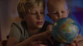 Il bambino sveglio che si siede a cattivo e che gioca appena con il globo ed suo fratello fa la società con la macchina fotografi stock footage
