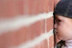 Il bambino sveglio con il radiatore anteriore squished contro il muro di mattoni Fotografie Stock