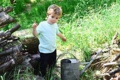Il bambino sveglio ha idea circa qualcosa Il grande innaffiatoio è davanti al ragazzino circondato da erba Il bambino piccolo vuo immagine stock libera da diritti