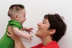 Il bambino sveglio ha tenuto dal suo punto di vista sorridente di profilo della madre Fotografia Stock