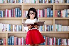 Il bambino sveglio legge il libro in biblioteca Immagini Stock