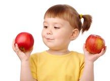 Il bambino sveglio sceglie fra due mele Fotografia Stock Libera da Diritti
