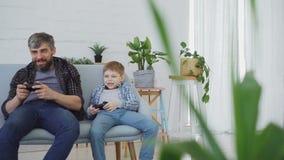Il bambino sveglio sta giocando il video gioco con suo padre allegro che è vincente e ritenente eccitato, essi sta ridendo e stock footage