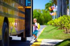 Il bambino sveglio sta salendo il bus, aspetta per andare a scuola Immagine Stock