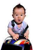 Il bambino sveglio usa il casco del motociclo Fotografia Stock