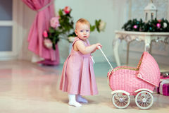Il bambino sveglio in vestito rosa rotola il passeggiatore sui precedenti di Fotografia Stock
