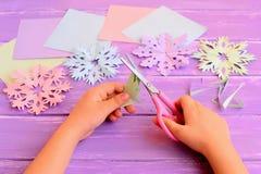 Il bambino taglia i fiocchi di neve da una carta Il bambino tiene le forbici e lo strato di carta piegato in mani Attività emozio Fotografia Stock