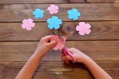 Il bambino taglia un fiore di carta Il bambino tiene la carta e le forbici in sue mani Fiori di carta messi su una tavola di legn Fotografia Stock