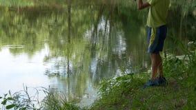 Il bambino teenager prende una canna da pesca sullo stagno archivi video