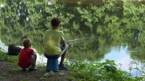 Il bambino teenager prende una canna da pesca sullo stagno video d archivio