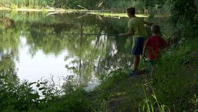 Il bambino teenager prende una canna da pesca sullo stagno stock footage