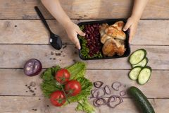 Il bambino tiene il contenitore di alimento con le ali di pollo arrostite fotografie stock