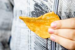 Il bambino tiene i chip in sua mano Alimenti industriali fotografia stock