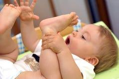 Il bambino tiene i piedi Fotografia Stock