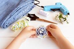 Il bambino tiene il fiore del denim della fibula in sue mani Fibula creativa del fiore facendo uso di vecchi jeans immagine stock libera da diritti