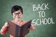 Il bambino tiene il libro con di nuovo al testo di scuola nella classe Immagini Stock