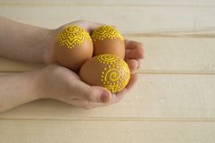 Il bambino tiene l'uovo marrone con un modello Uova marroni dipinte Fotografia Stock Libera da Diritti