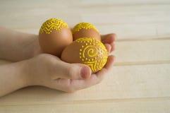 Il bambino tiene l'uovo marrone con un modello Uova marroni dipinte Fotografia Stock