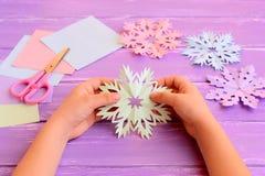 Il bambino tiene un fiocco di neve di carta in mani Il bambino mostra la decorazione del fiocco di neve Carta colorata, forbici,  Immagini Stock