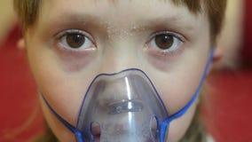 Il bambino triste nella maschera di respirazione dell'ospedale per inalazione, ragazza in ospedale è curato da inalazione video d archivio
