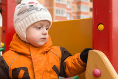 Il bambino triste in tempo piovoso ad un campo da giuoco Immagine Stock Libera da Diritti