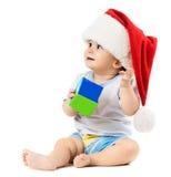 Il bambino in un cappello di Natale ha voluto qualcosa Fotografia Stock